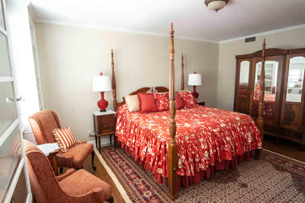 The Julia Suite with beautiful antiques, red themed linens, chair and dresser