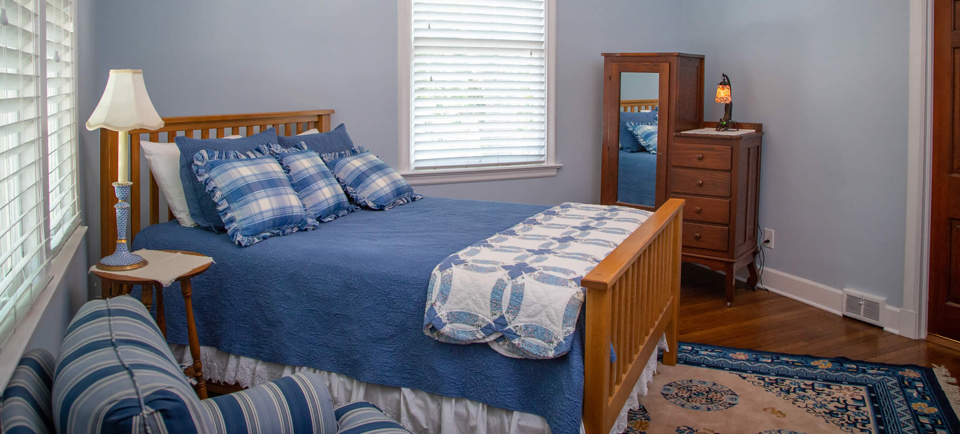 valpo inn guestroom with bed, blue bedspread, table with lamp
